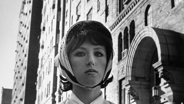 Une jeune femme porte un foulard sur ses cheveux devant un bâtiment en béton.