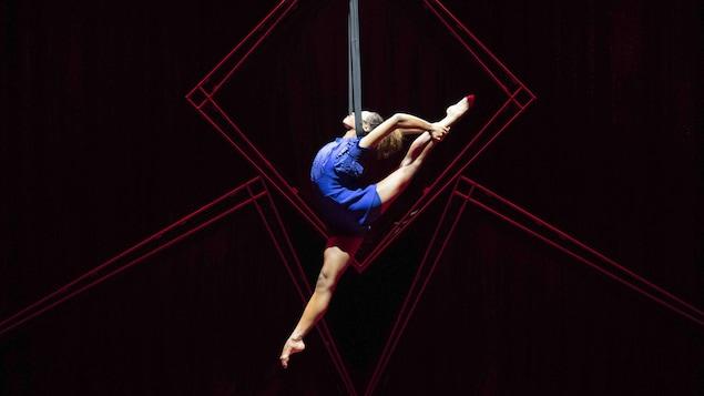 L'acrobate est cambrée dans les airs et accrochée à un tissu bleu. Elle fait le grand écart et tient sa jambe gauche par les mains derrière elle.