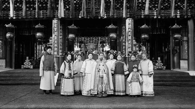 L'impératrice chinoise entourée de 9 personnes, devant un monument chinois.