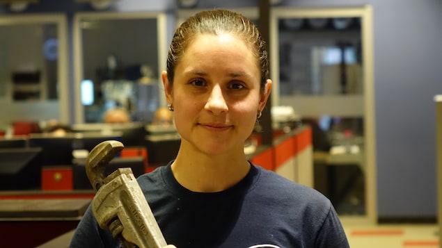 Claudie Morissette tient une clé à molette.