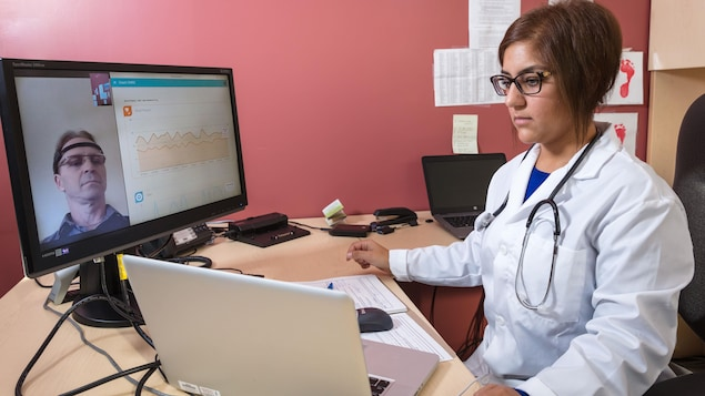 طبيبة تعاين مريضاً عن بُعد، ويبدو وجه المريض على شاشة حاسوب أمامها.
