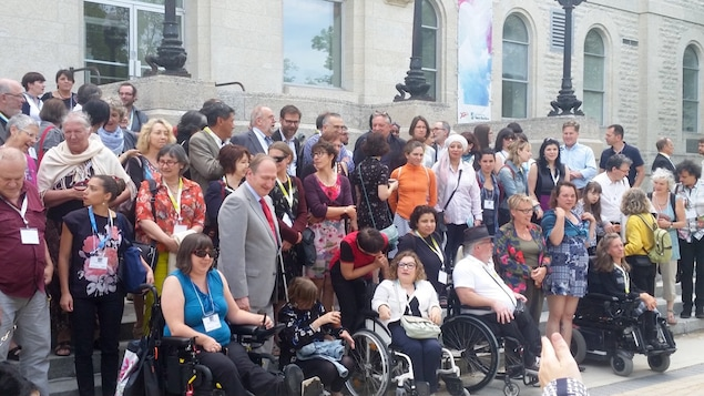 Personnes réunies pour une photo de groupe, au premier rang, des personnes en chaises roulantes