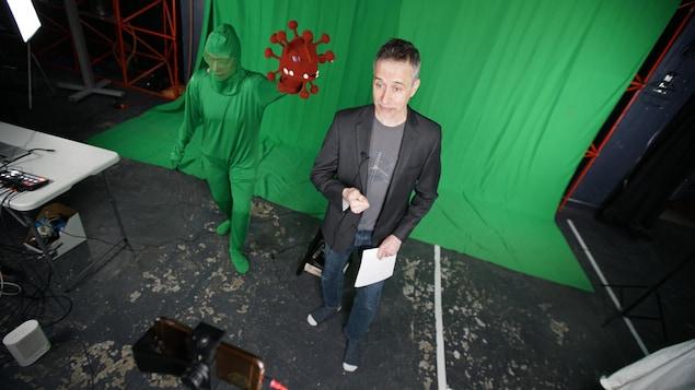 Joël Leblanc dans un studio d'enregistrement parle devant un écran de téléphone, à ses côtés un figurant porte une représentation du coronavirus.