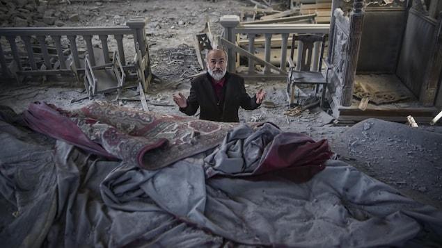 Un homme dans la soixantaine prie à l'intérieur d'une église endommagée.