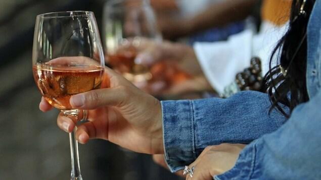 Un verre de vin contenant un liquide rosé dans la main d'une personne.