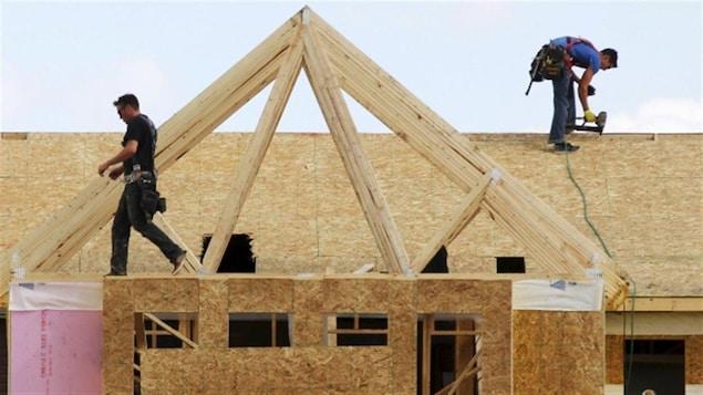 Des travailleurs de la construction construisent une maison à Calgary en 2015.