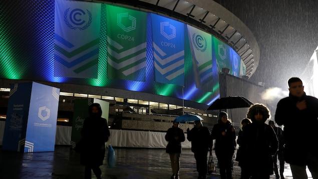 Des personnes marchent sous la pluie devant un stade orné de banderoles annonçant la COP24.