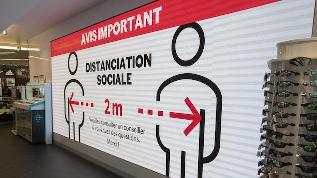 L'Intérieur du magasin Sports Experts avec un panneau rappelant les règles de distanciation sociale.