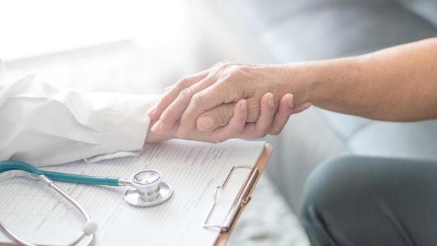 Un médecin tient la main d'une femme souffrant de la maladie de Parkinson.