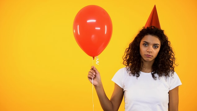 Une jeune femme qui a l'air triste tient un ballon de fête, sans enthousiasme.