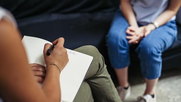 Une femme discute avec une psychologue durant une séance de psychothérapie.