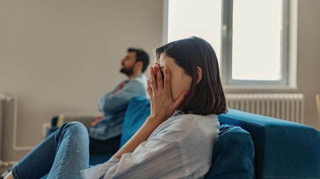 Un homme et une femme se disputent sur une sofa.