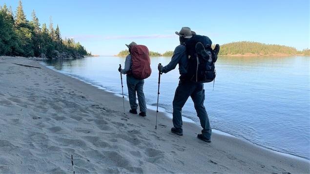 Une femme et un homme portant des sacs à dos marchent sur un rivage.