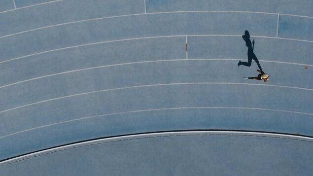 Une coureuse et son ombre vues de haut sur une piste bleue.