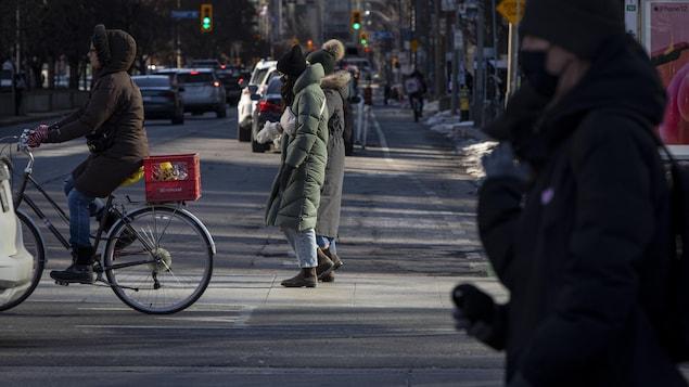 Des gens vêtus de vêtements d'hiver traversent une intersection de Toronto.