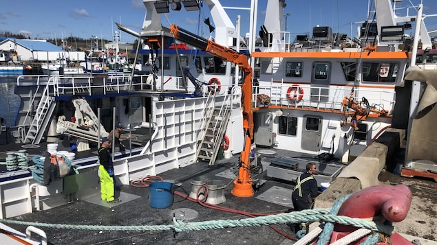 Des pêcheurs sur un crabier rangent de l'équipement.