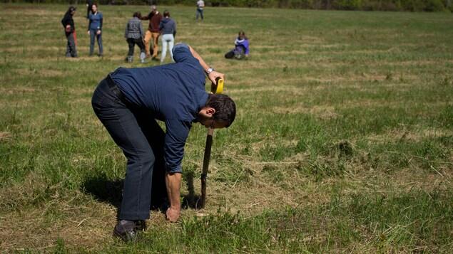 Un homme plante un arbre.