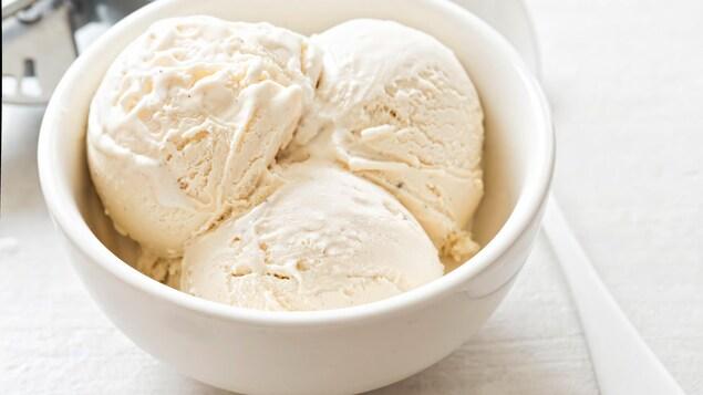 Un bol de crème glacée à la vanille est déposé sur une table.