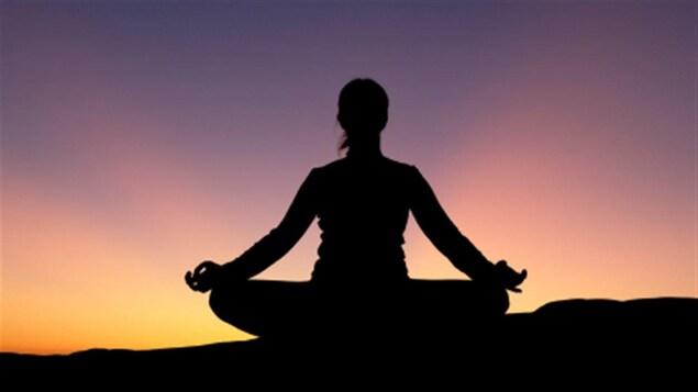 Silhouette d'une personne assise en position de méditation au coucher du soleil.