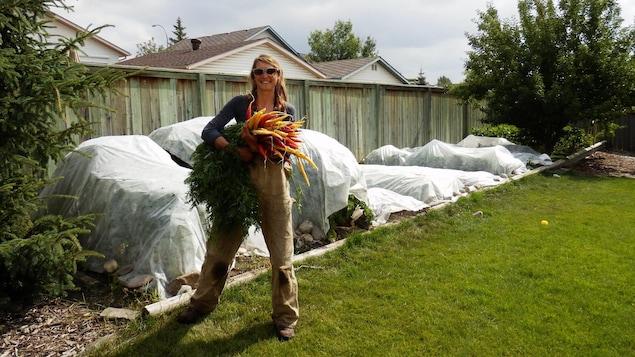 Delphine Pugniet, fermière tenant une botte de carottes dans un jardin.