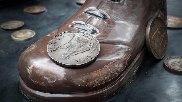 On voit une chaussure géante avec une pièce sur le dessus et d'autres pièces de monnaie autour.
