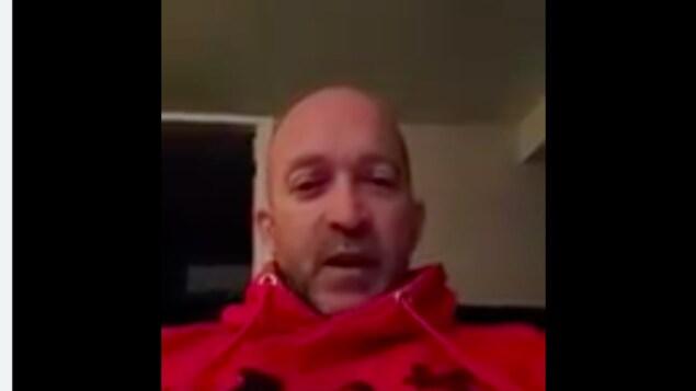Un homme dans une capsule vidéo sous de l'écriture.