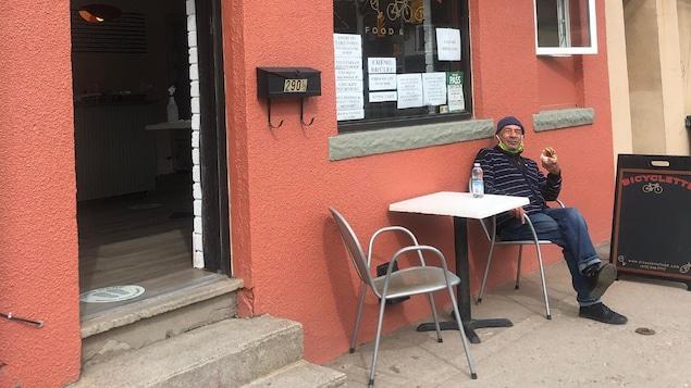 Jean-Pierre Centeno est assis à l'extérieur, devant son restaurant aux murs ocres.