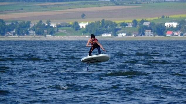 La planche semble flotter dans les airs sur un lac avec un homme dessus pour la manipuler.