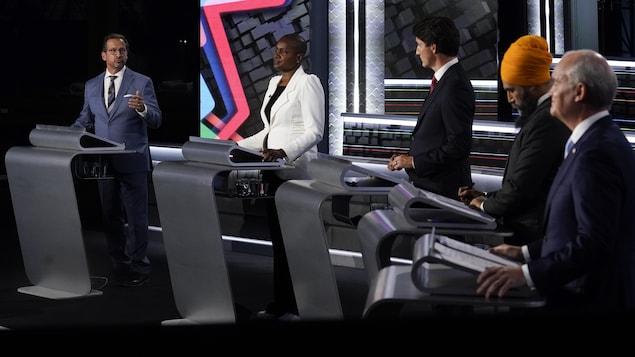 Les cinq chefs sont debout derrière un lutrin. Yves-François Blanchet et Justin Trudeau se regardent lors d'un échange.