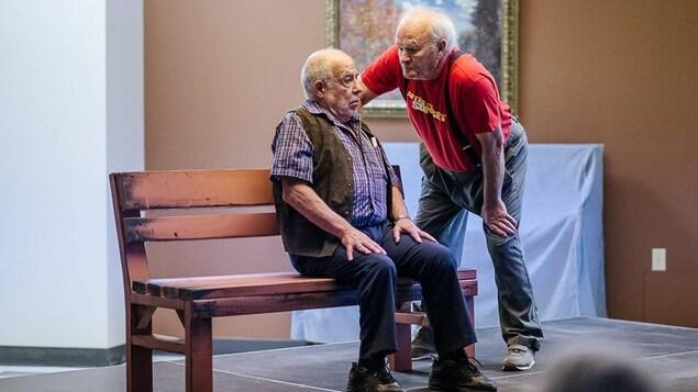 Un homme est assis sur un banc. Un autre homme, debout, le regarde. Ils sont sur une scène.