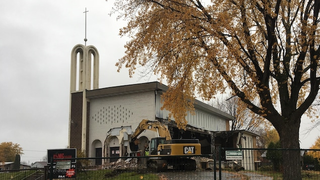 Une pelle mécanique en train de détruire une église à l'architecture moderne.