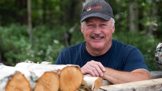 Denis Picard, propriétaire de la bleuetière Bleu Nord à Gallix (dehors, appuyé sur une corde de bois, en saison estivale)