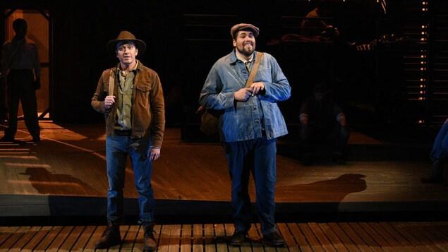 Les deux hommes se tiennent debout sur une scène.