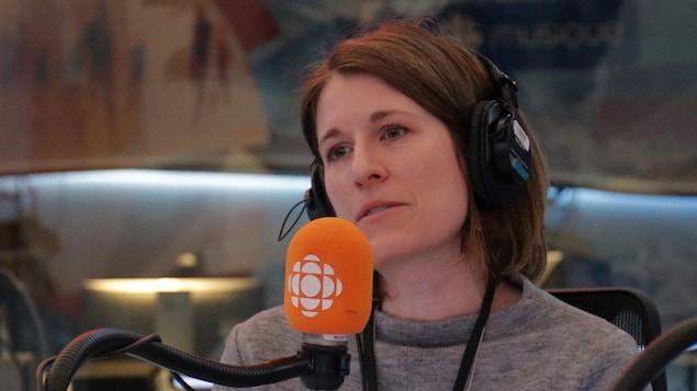 France-Isabelle Langlois devant un microphone dans un studio de radio.