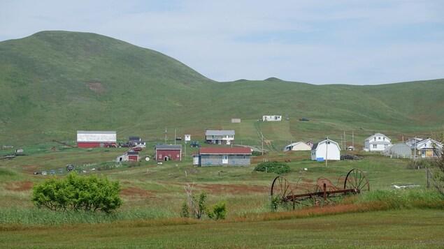 Un paysage bucolique se dresse à l'horizon, avec des petites maisons et des collines.