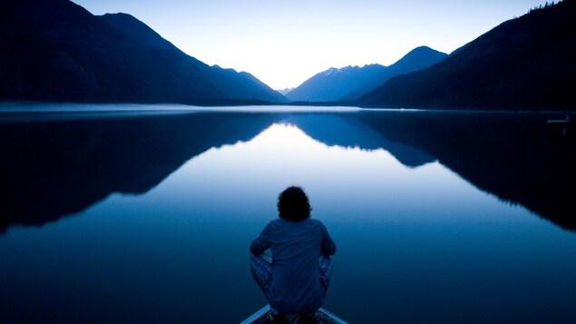 Une personne regarde un lac silencieux.