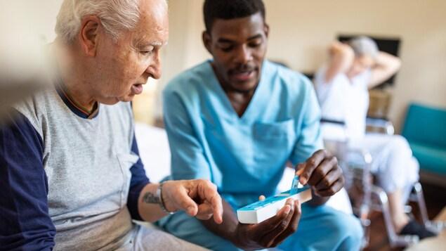 Assis sur un lit, un infirmier montre une boîte de médicaments à un patient âgé.