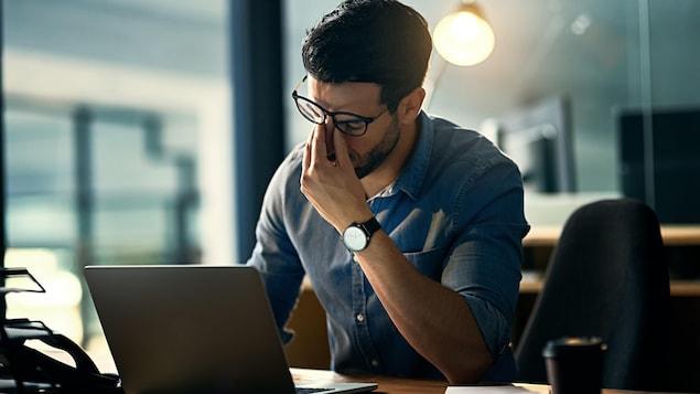 Un homme se tient le nez en signe d'épuisement devant son ordinateur portable posé sur une table.