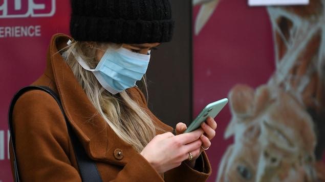 Une femme coiffée d'une tuque en laine et le visage recouvert d'un masque médical est penchée sur son téléphone cellulaire.