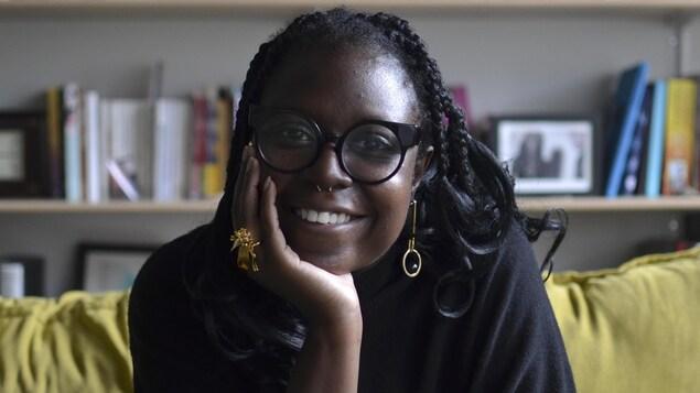 La jeune femme noire sourit en tenant le menton avec une main.