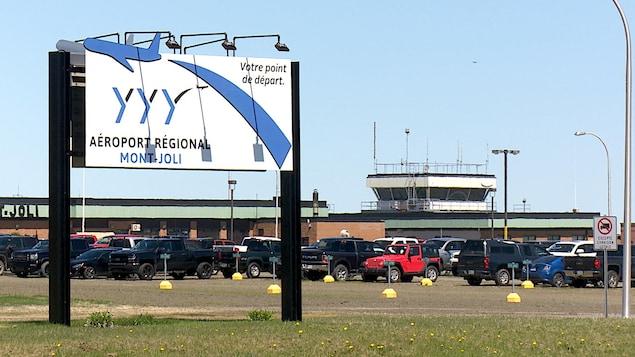L'affiche de l'aéroport et des bâtiments derrière.