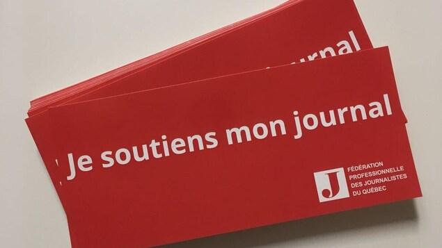 Une carte rouge où il est écrit : «Je soutiens mon Journal»