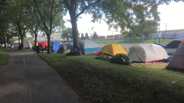 Des tentes installées le long d'un boulevard.