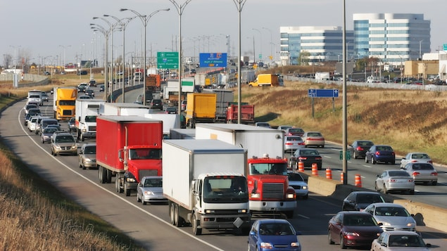 Des camions et des voitures roulent sur une autoroute.
