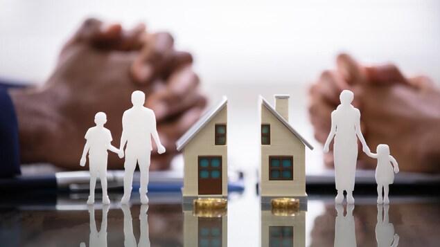Une image représentant la séparation d'une famille avec d'un côté, une figure d'un père et d'un enfant avec la moitié de la maison et de l'autre celle d'une mère avec un enfant et l'autre parie de la maison..