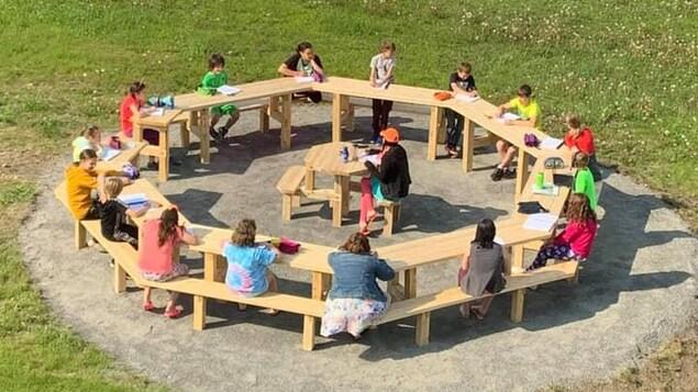 Des enfants autour d'une grande table à pique-nique.