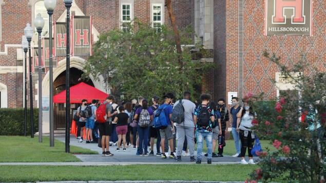 Des étudiants doivent faire la queue pour que la température soit vérifiée avant d'entrer dans leur école.