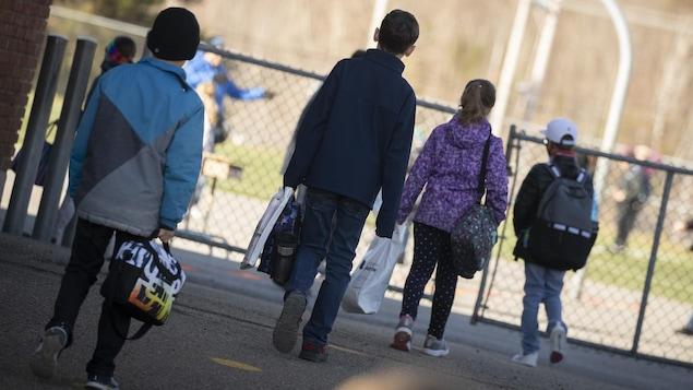 Des enfants gardent une bonne distance entre eux avant d'entrer dans une école.