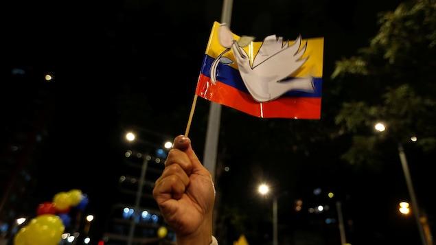 Un oiseau de la paix collé sur un drapeau de la Colombie soutenu par une main.