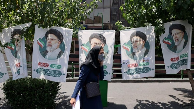 une Iranienne passe devant les bannières de l'ultra-conservateur Ebrahim Raisi, candidat à la présidence.